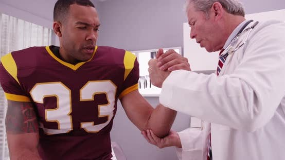 Thumbnail for Young african american football player having doctor examine arm
