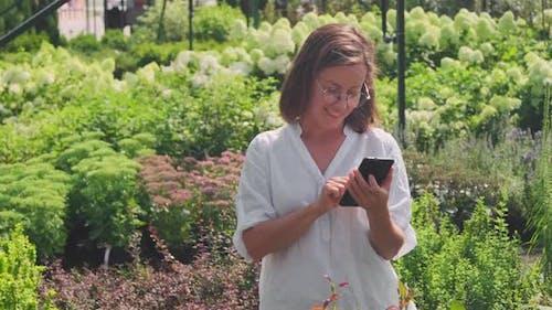 Woman Taking Shots Of Plants In Garden On Phone