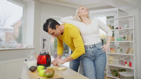 Cheerful Beautiful Woman Leaning on Man Cutting Banana for Healthful Dieting Smoothie