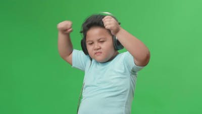 Side View Of Asian Little Boy Listening To Music With Headphones And Dancing In The Green Screen