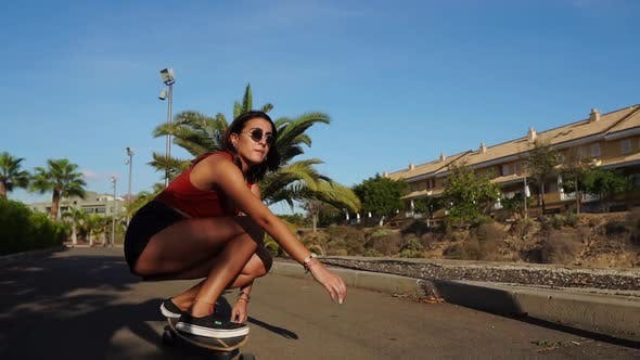 Cover Image for A Young Woman in the Summer Riding a Longboard Near the Palm Trees in Shorts and Sneakers