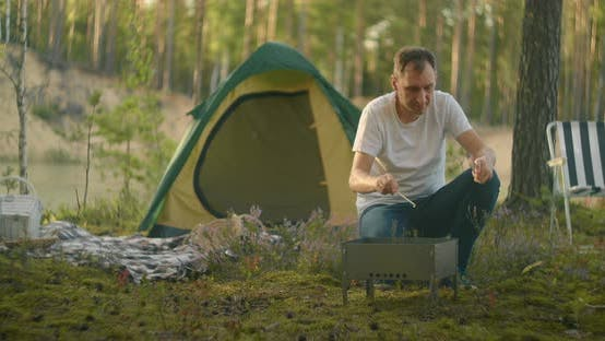 Thumbnail for Tourist Is Living in Forest Camp Alone, Inflaming Coal in Chargrill for Cooking Dinner, Trip in