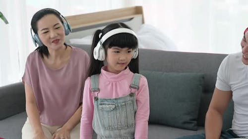 Concept of family stay at home, The daughter was wearing headphones to music and practicing dancing.