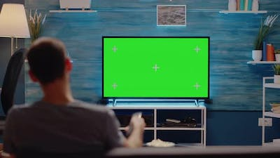 Man Using TV Remote on Green Screen Background