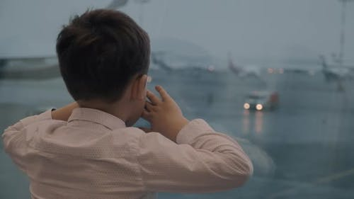 Boy waiting for the flight and looking at airplanes outside