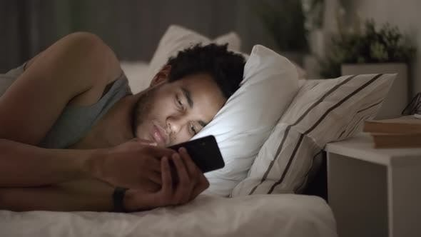 Thumbnail for Man Browsing Internet with Smartphone at Night