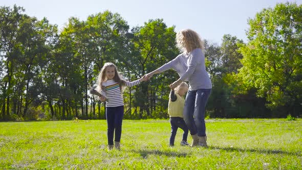Thumbnail for Blond Caucasian Woman with Curly Hair Dancing with Two Pretty Little Girls on the Meadow