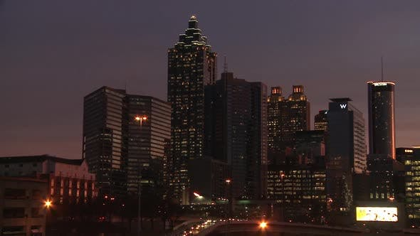 Thumbnail for Panning, medium shot from left to right of the Atlanta Skyline at night with illuminating lights.