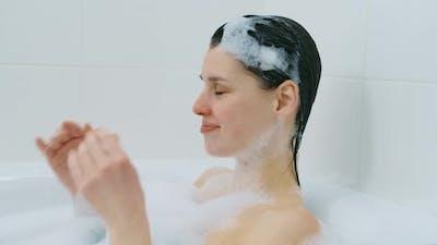 Caucasian Woman Lying Naked in Bath with Foam