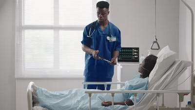 A Male Doctor is Talking to a Patient Lying on a Hospital Bed in a Hospital Ward