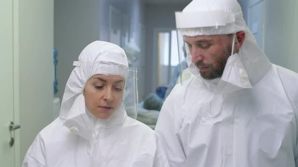 Doctors in Protective Uniform Walking and Talking in Hospital