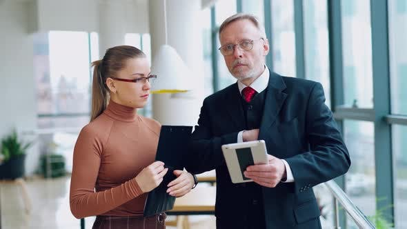 Boss is giving a pen to a woman assistant for signing papers in office