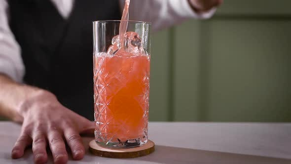 Thumbnail for A Close-up in the Night Bar. The Bartender Pours the Finished Cocktail Into the Glass. A Beautiful
