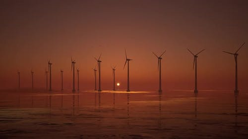 3D animation of offshore wind turbines at sunset. Wind Farm, renewable energy.