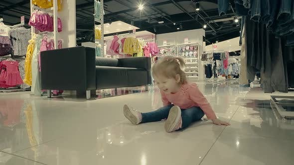 Thumbnail for Little Child in Clothing Store Sits on the Floor and Laughs, Slow Motion