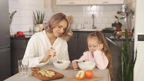 Young Happy Family Mother and Little Daughter Sitting at the Kitchen Table Smiling Enjoying