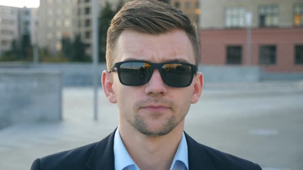 Thumbnail for Portrait of Young Businessman in Sunglasses Walking in City Street. Handsome Business Man Stepping