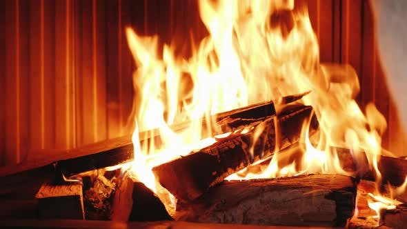 Thumbnail for A Man Puts Oak Firewood in a Fireplace Insert. Raises the Glass Guillotine Type, Puts the Log in the