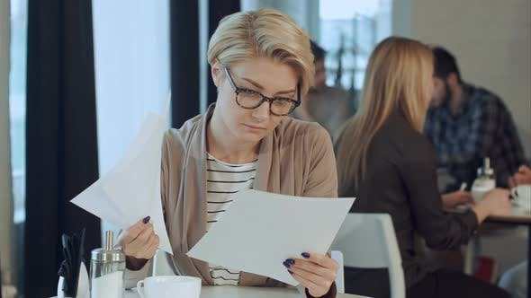 Thumbnail for Businesswoman Working with Documents in Coffee Shop