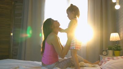 Mom With Daughter At Home On The Bed