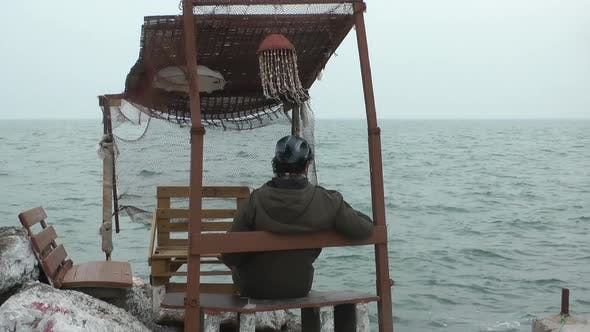 Thumbnail for Lonely Man Sitting In Wooden Historical Fisherman Building And Looking Sea