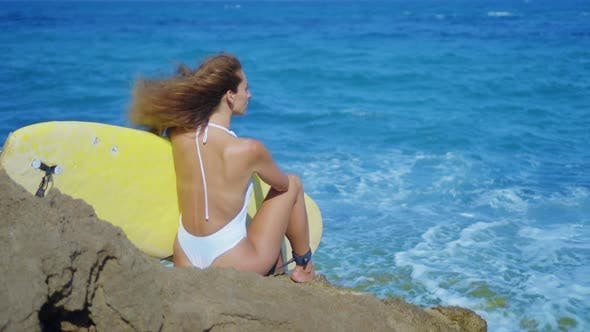 Thumbnail for Surfer Girl Sits on a Beautiful Rocky Beach with Board. Powerful Waves Hit the Rocky Shore
