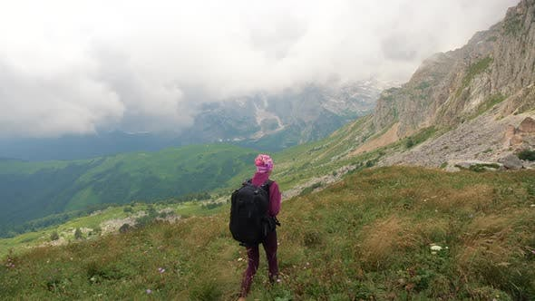 Young Woman with Backpack Is Hiking in Beautiful Caucasian Mountains. Lady Walks Towards the Summit.