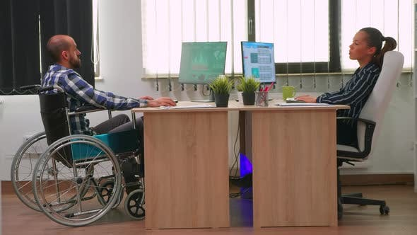 Businesswoman Talking with Paralysed Colleague
