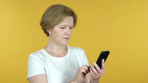 Old Woman Excited for Success While Using Smartphone Isolated on Yellow Background