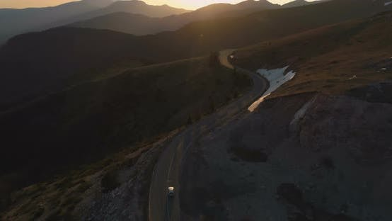 White Car Driving on Winding Remote Mountain Road. Sunset Lights Shine Over Mountain Peaks