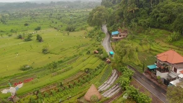 Aerial View Following a Truck Driving Through Rural Countryside and Villages in Bali