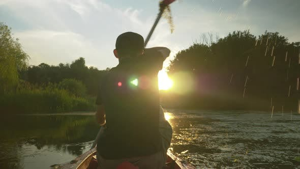 Thumbnail for Paddle rowing on calm river at sunset. Man is floating in canoe on summer vacation.