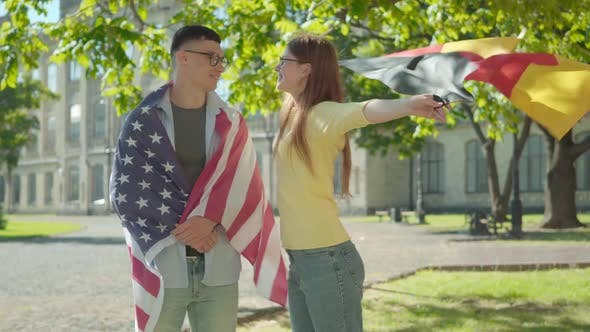 Thumbnail for Portrait of Happy American Male Student Wrapped in National Flag Standing with Smiling Beautiful