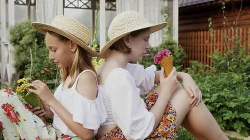 Cute Teenager Girls in Straw Hat Sniffing Wildflowers in Countryside Homestead While Summer Vacation
