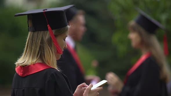 Thumbnail for Smiling Blonde Graduate Standing Near Friends and Texting on Smartphone