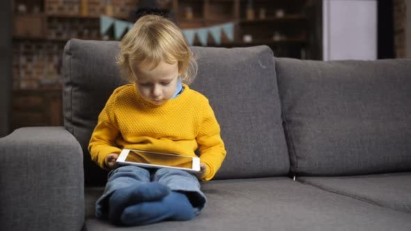 Thumbnail for Cute Blond Toddler Boy Using Touchpad on Sofa