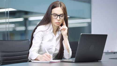 Businesswoman Writing in Journal and Using Laptop