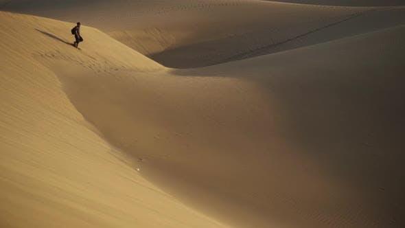 Thumbnail for Man Walking On Sand Dunes Through Desert