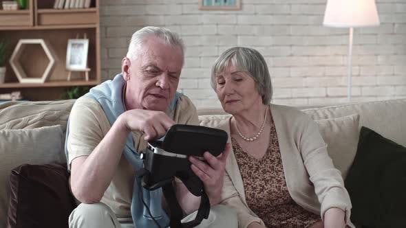 Thumbnail for Concentrated Elderly Couple Inspecting VR Goggles