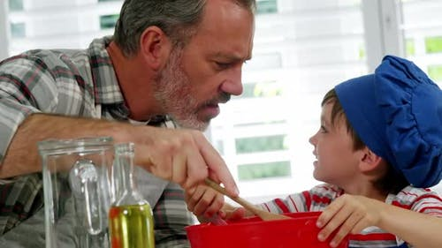 Father and boy mixing dough in bowl