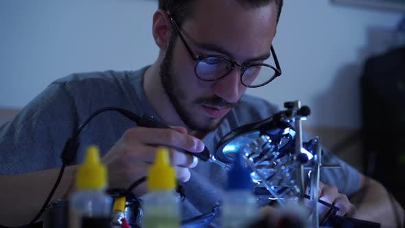 Thumbnail for Portrait of Successful Young Bearded Man in Glasses Working with a Soldering Iron at His Working