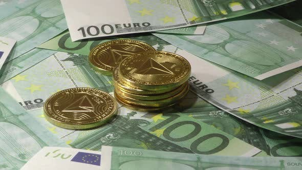 Gold Tron Coin TRX Coins Rotating on Bills of 100 Euro Banknotes. Worldwide Virtual Internet