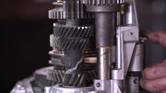 Car Mechanic Controls Transmission Gears Manually
