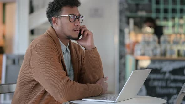 Thumbnail for African Man Laptop Talking Smartphone