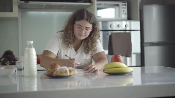 Thumbnail for Young Caucasian Obese Woman Calculating Calories Sitting in Kitchen in the Morning. Portrait of