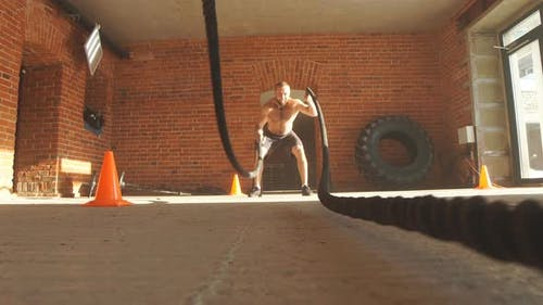 Muscular Powerful Determined Man Training with Rope in Gym.