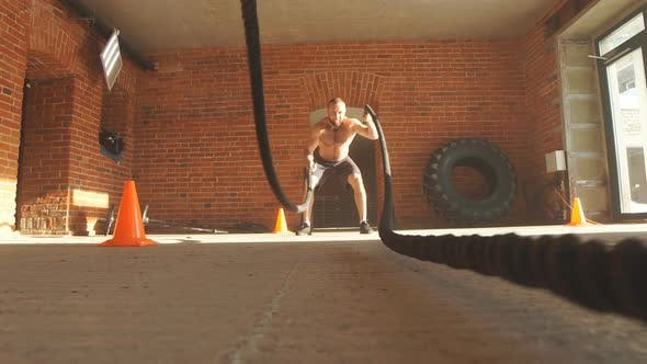 Thumbnail for Muscular Powerful Determined Man Training with Rope in Gym.