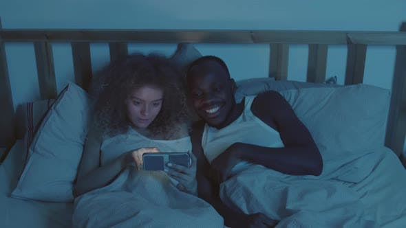 Thumbnail for Young Man and Woman Using One Cellphone in Bed