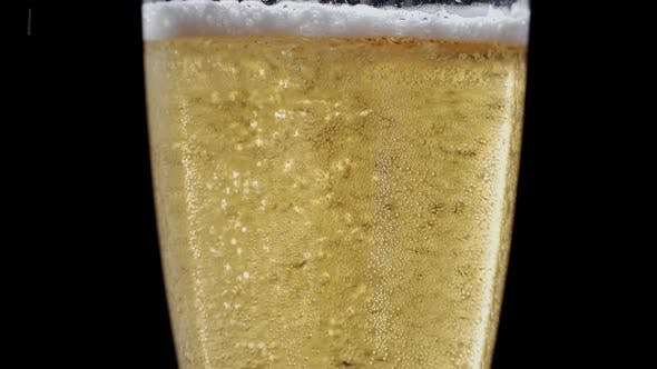 Beer Is Pouring and Foaming in Glass on Black Background Closeup Slow Motion