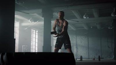 Guy Having Fitness Training with Hammer